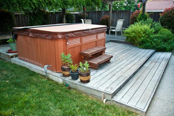 outdoor hot tub with leather cover deck setup on the backyard