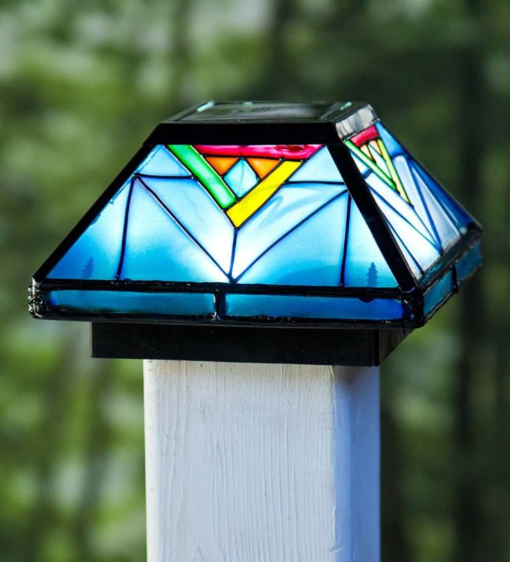 Solar-powered Artisan glass cap lights installed on a fence post or white railing isolated in green background.