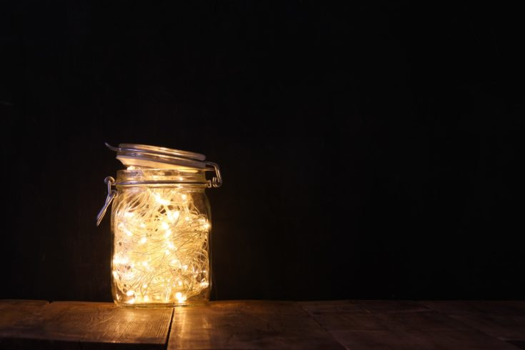Mason jar filled with lighted string lights on top of a wooden table and a white background.
