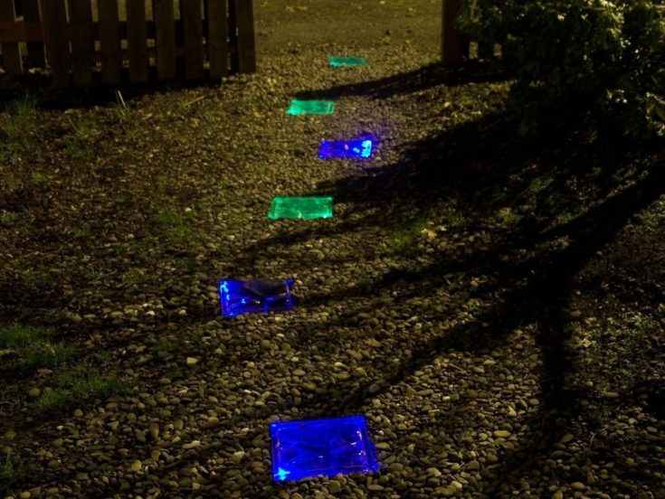 Pathway lighted with a solar glass brick in green and blue color.