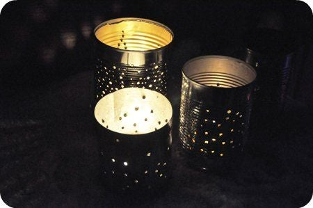 Tin cans filled with lighted solar lights in a dark background
