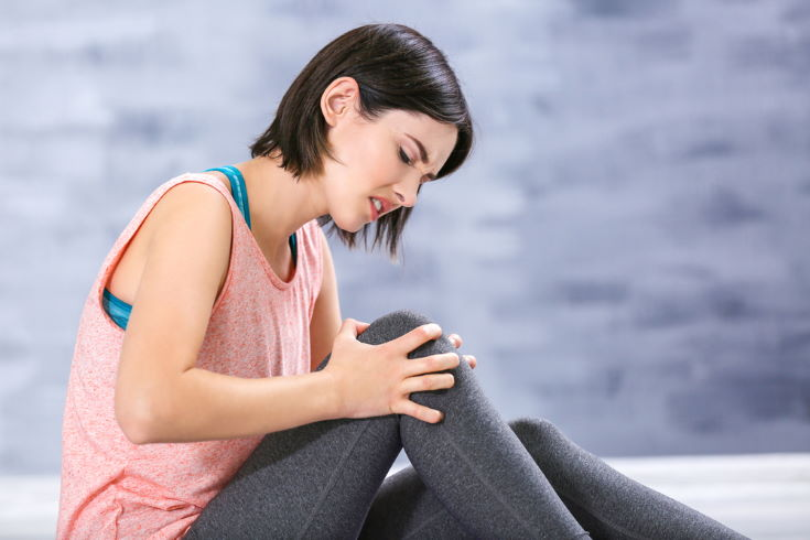 Beautiful young woman suffering from knee pain indoors