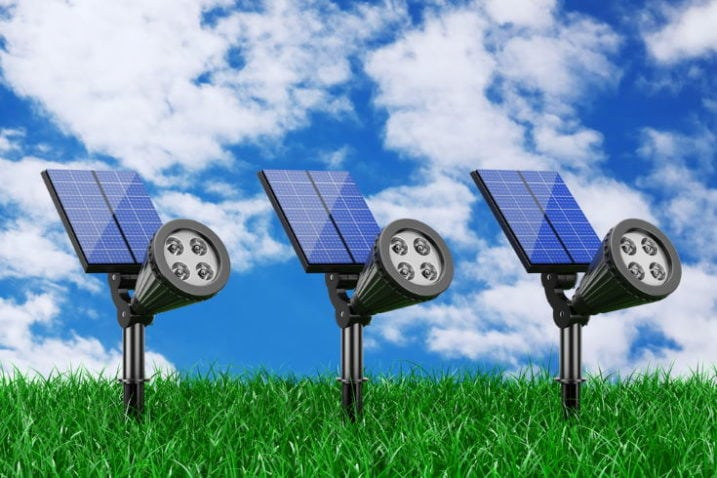 Outdoor Garden LED Spotlights with Solar Panel in Grass on a blue sky background
