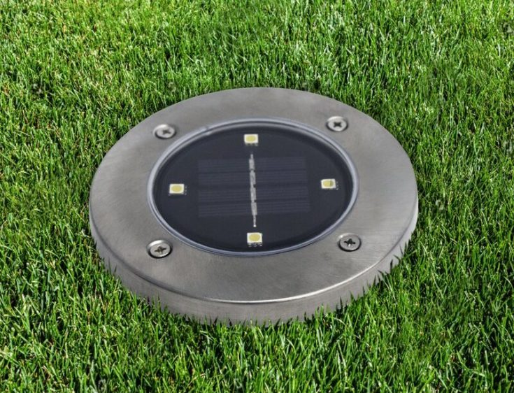 bell and howell disk light layed on a green grass lawn.