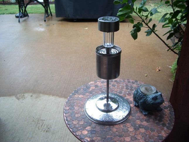 DIY solar light lamp on top of a round table with a figurine frog on the side.