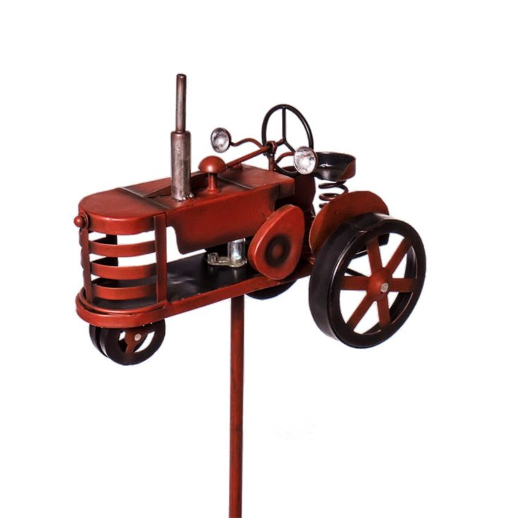 Red metal tractor design attach on a pole with a solar light on it. Standing in a white background.