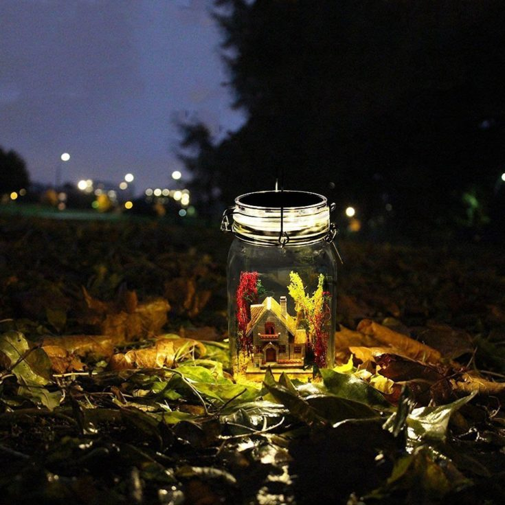 Miniature mason jar filled with a miniature small house and a solar light