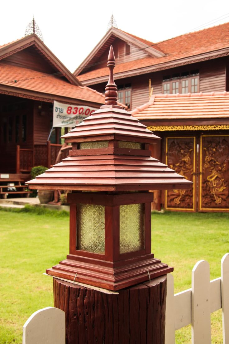 Oriental inspired post tops mounted on a wooden fence post outside.