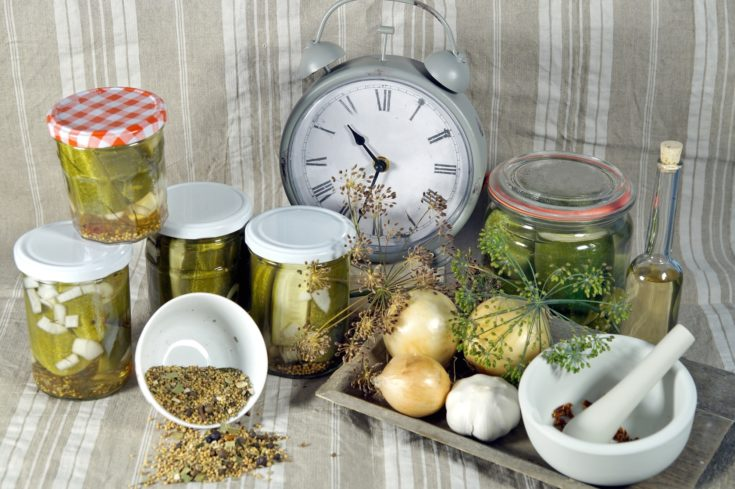 Time to pickled. to keep long time. Pickled cucumbers in glass jar with clock, herbs and dill spices, on a fabric linen background.
