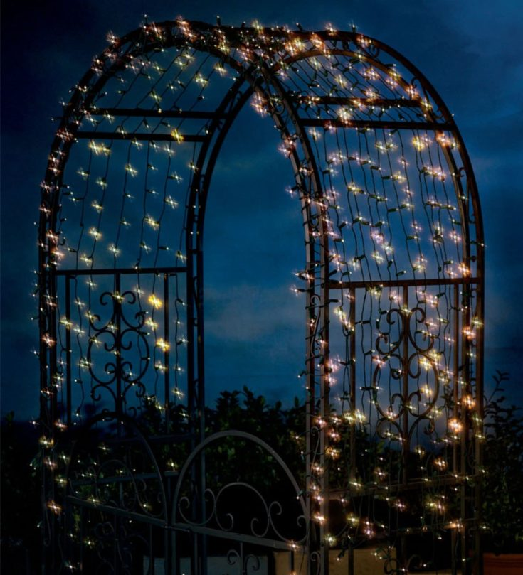 Solar string lights decorated on a trellis arch out in the backyard.
