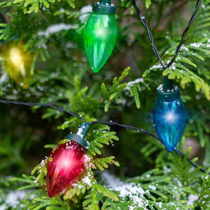 Touch Of ECO Solar LED Christmas Bulb String Lights in red,green,blue and yellow decorated on a christmas tree.