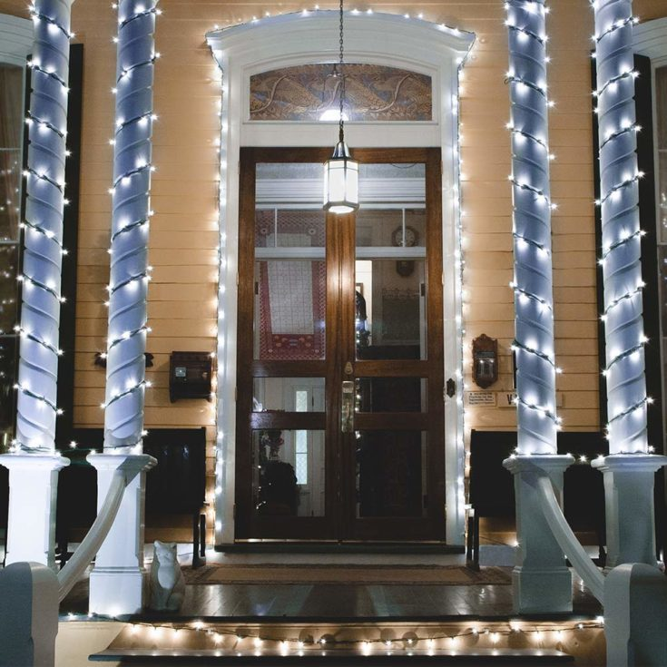 White lit string of lights decorated on front door post and pillars.