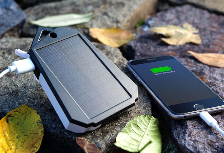 Touch of ECO Sunvolt Dual USB Solar Powered Charger charging a smart phone place on top of a flat surface rocks.