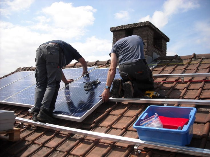 Men installing solar panel on the roof