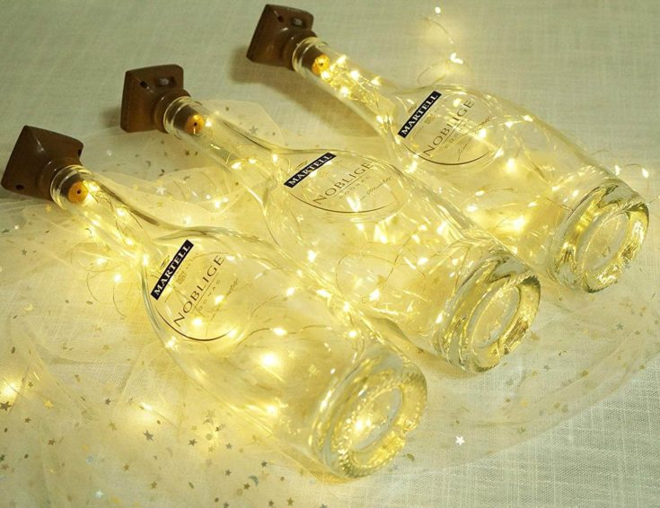 3 Martell wine bottle with lighted solar string lights inside layed in a lace clothing.