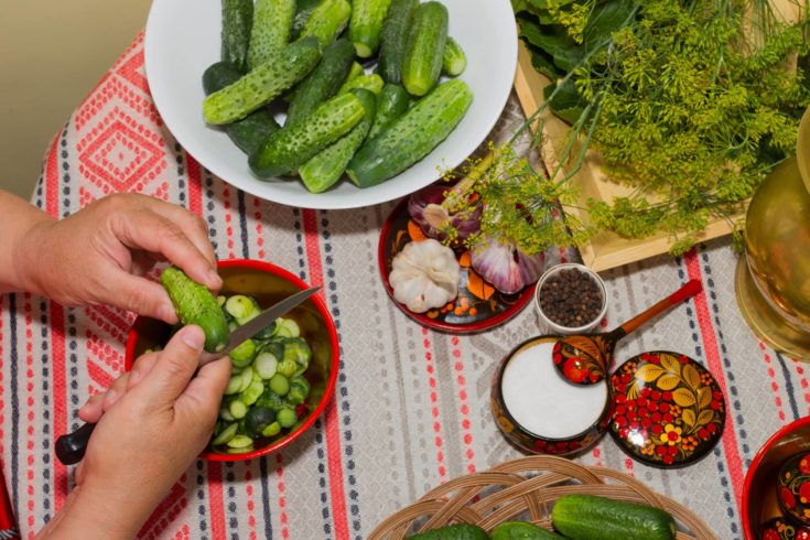 Pickling cucumbers, pickling - hands close-up, cucumber, herbs, spices, salt, hohloma, Russian style. Recipes, step execution. Harvesting vegetables in store.