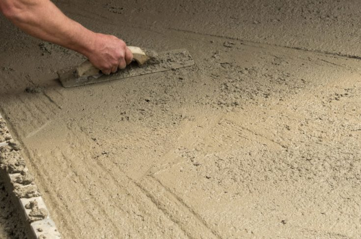 A worker finishes a fresh concrete floor