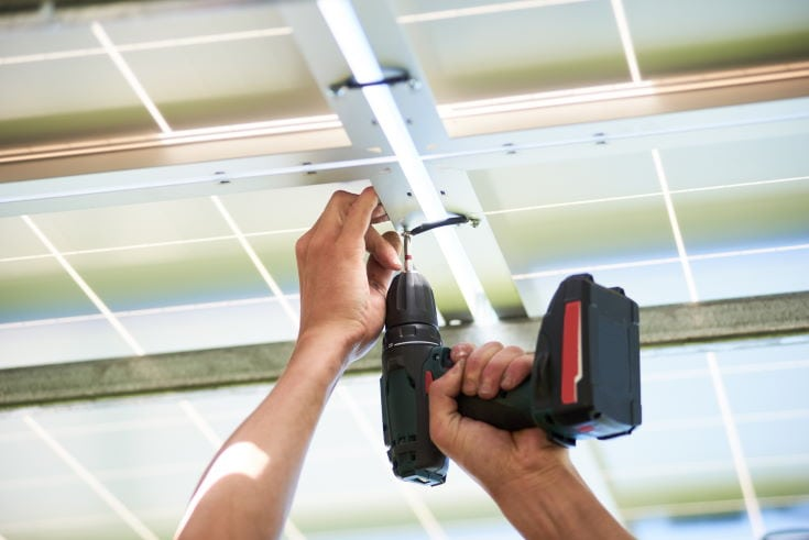 Worker using drill by solar panels installing. Innovative high-tech exterior. Modern solution for natural resources saving, using renewable solar energy. Environment friendly. New technologies.