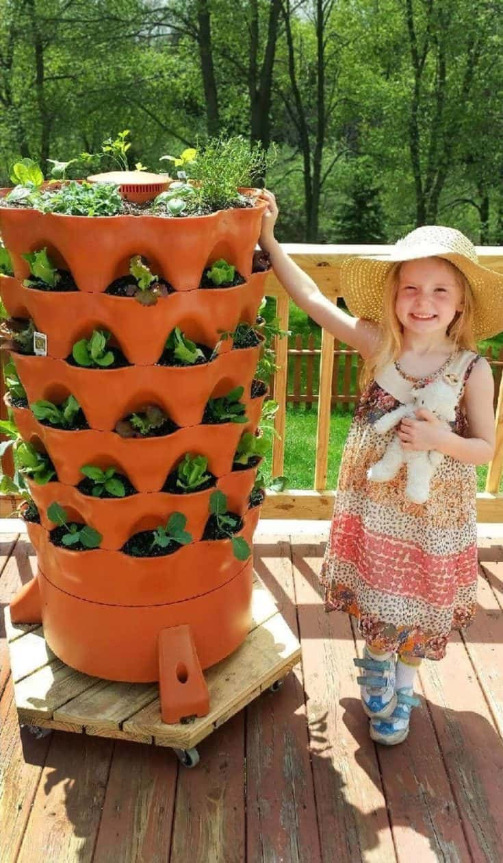 Young girl holding on garden tower with plants outside.