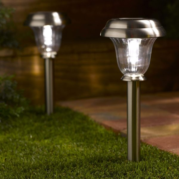 Two solar path lights installed on green lawn, beside a bricks pathways.