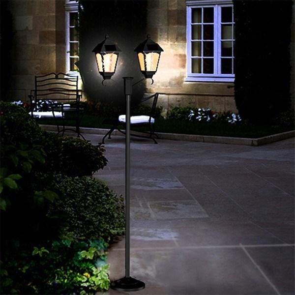 Solar post light standing beside a green bush outside lobby of the house.