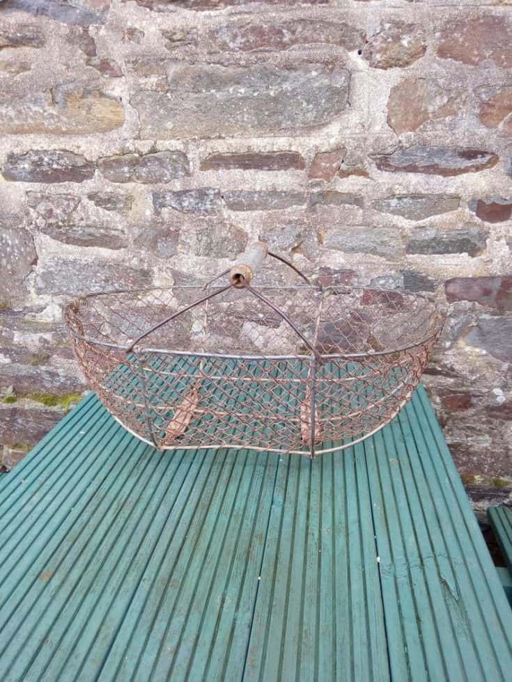 Old basket on top of a wooden table.