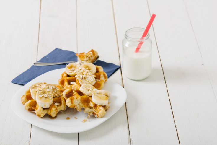 Homemade waffles with fruits on white vintage table. Selective focus and small depth of field.