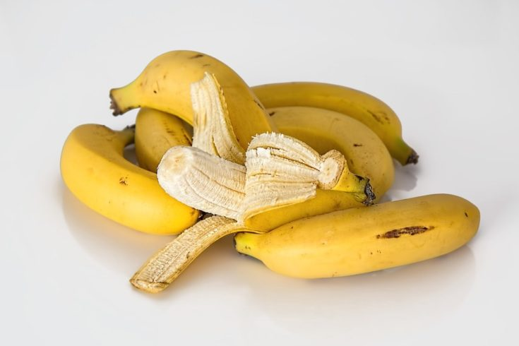Ripe bananas with one peeled in a white background.