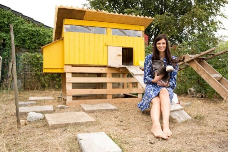 a smiling woman holding a chicken with a yellow chicken coop at her back