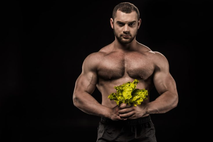 Young confident shirtless sportsman holding Lettuce salad leaves and looking at camera