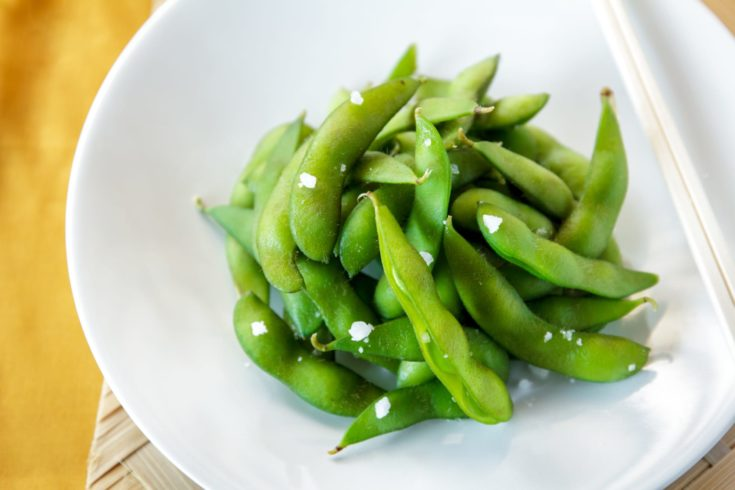 close up portrait of japanese food edamame nibbles, boiled green soy beans