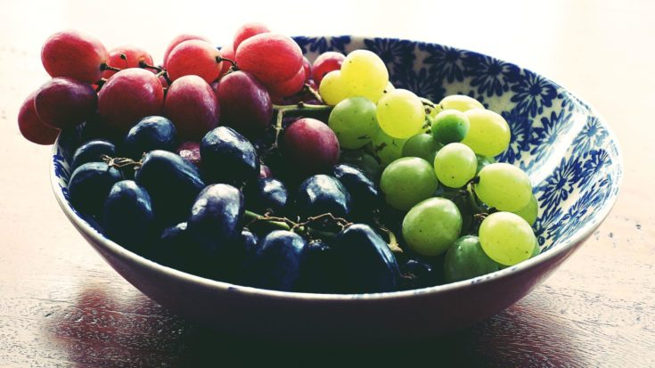 Three varieties of grapes in a ceramic bowl.