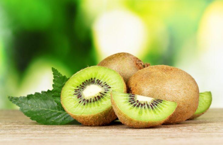 Juicy kiwi fruit on wooden table on green background