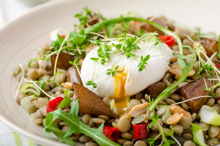 Healthy summer lentil salad with caramelized pear, arugula and poached egg soft on top