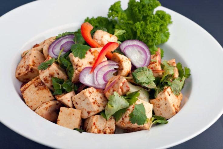 Fresh Thai food stir fry with tofu presented on a round white dish.