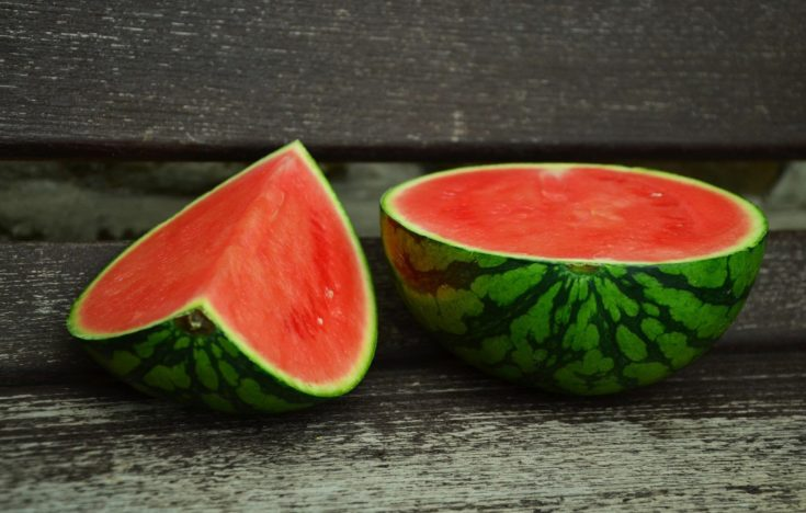 A sliced red watermelon fruits on a wooden bench.