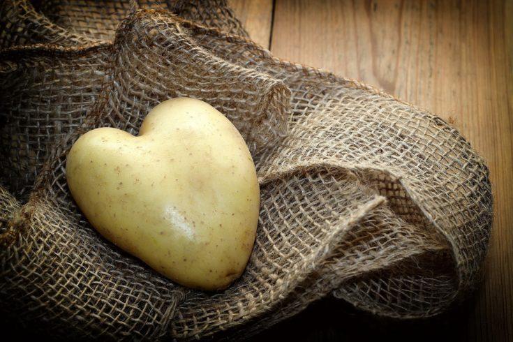 Heart shaped potato on a brown net sack.