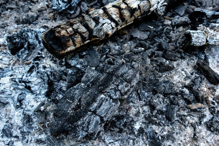 Charred wood and ash in an extinguished fireplace in closeup