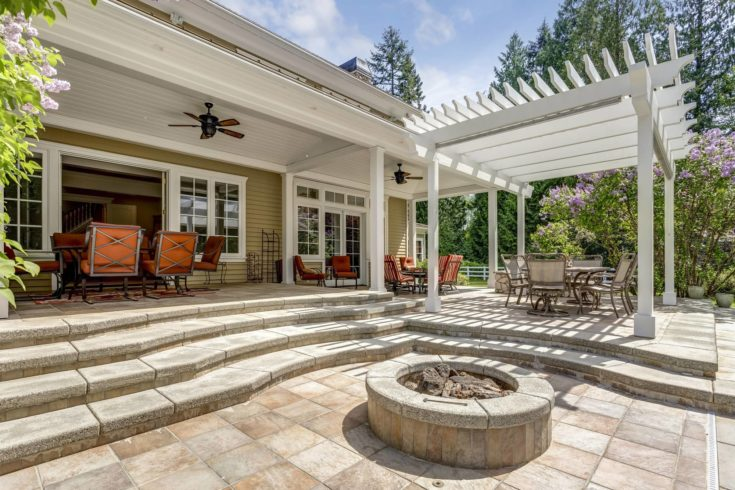 Lovely outdoor deck patio space with white pergola, fire pit in the backyard of a luxury house.