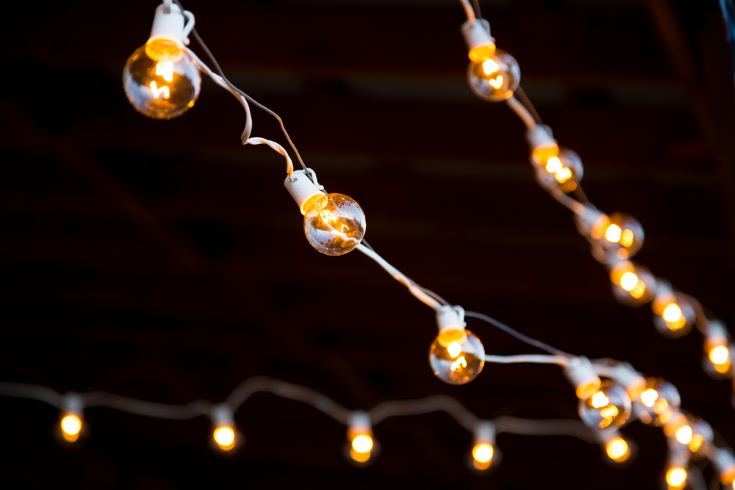 Lights are strung up and hung for this outdoor night time wedding reception.