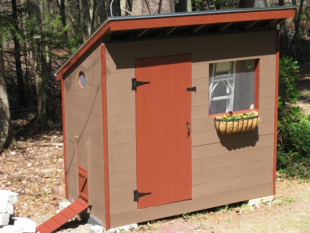 a small coop painted with orange and brown