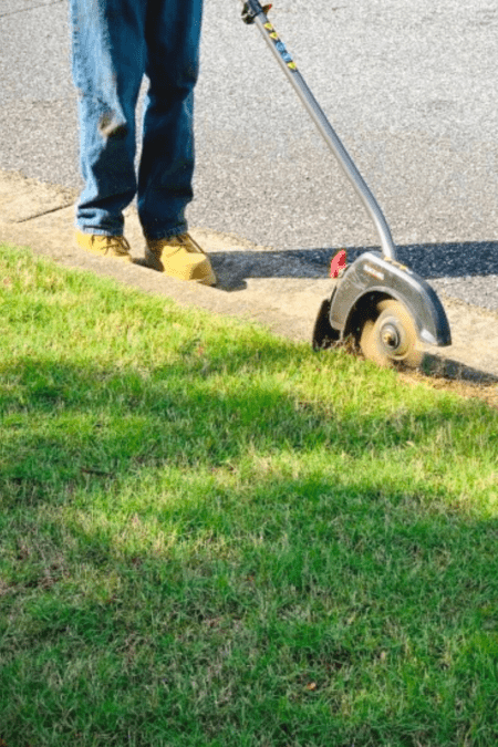 trimming edge of lawn with edger at curb