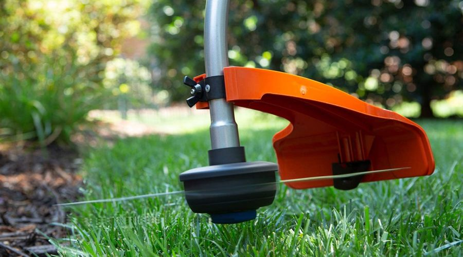 Close-up of a Husqvarna 952711952 string trimmer working on the edge of a garden bed.
