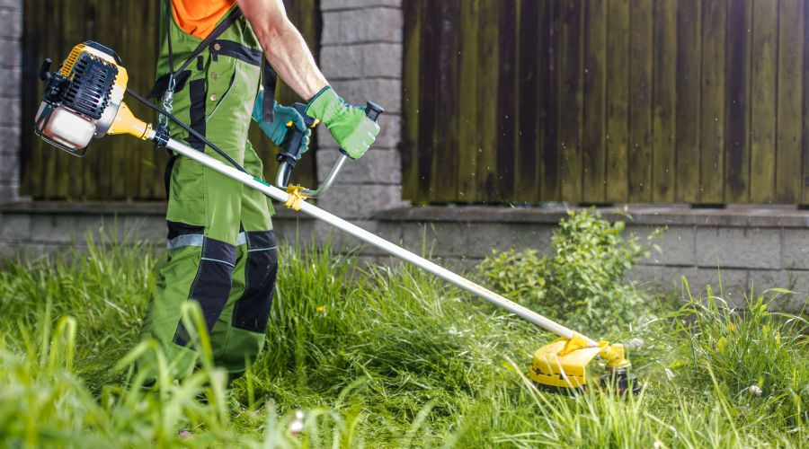 Man trimming grass with a string weed eater.