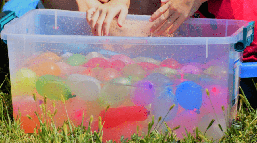 A very colorful tub of water balloons sitting in the grass with hands reaching in to grab some.
