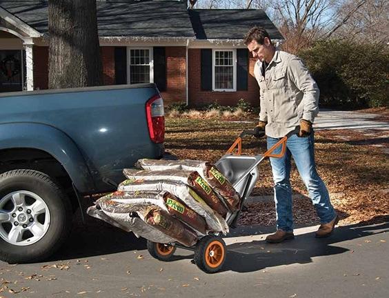 man pushing sacks of soil loaded onto a steel wheelbarrow