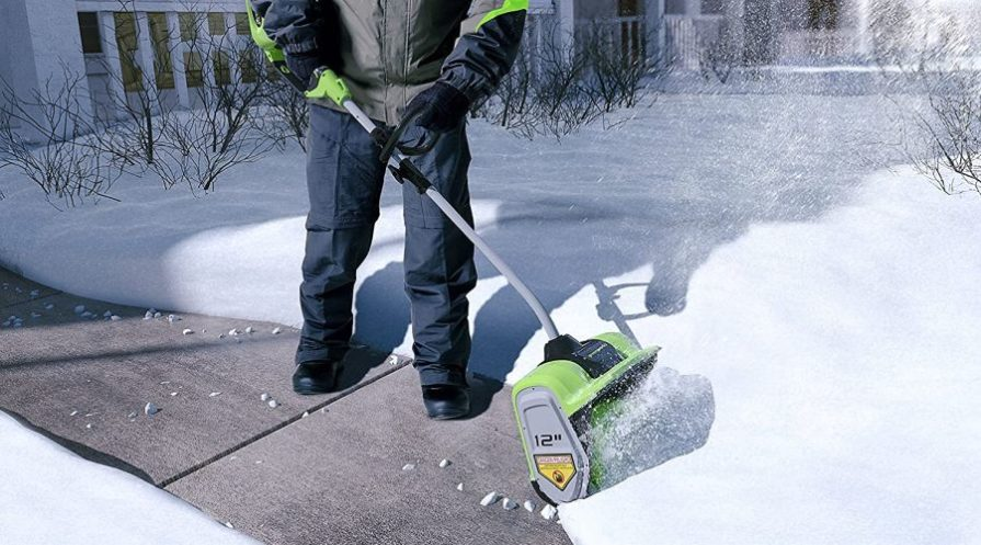 Man pushing a cordless electric snow shovel through a few inches of snow.