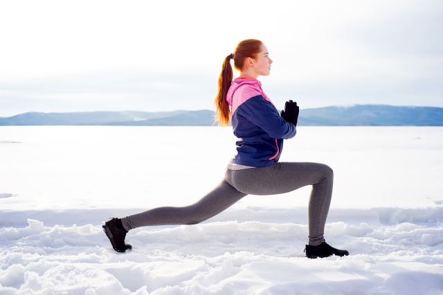 woman doing Yoga stretching in a winter wonderland