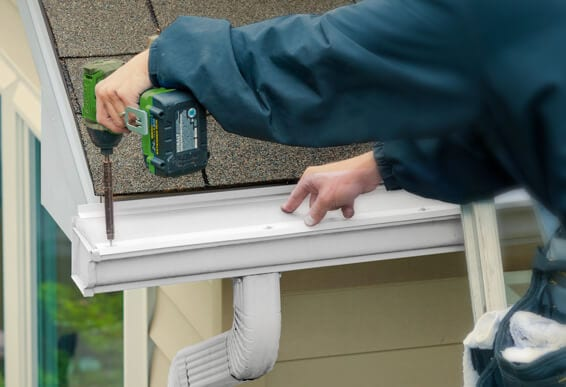 Man installing LeafFilter with a cordless drill into the eaves.