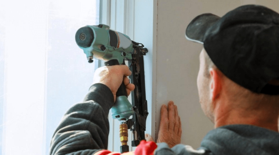 man in hat and jacket using brad nailer in window frim work